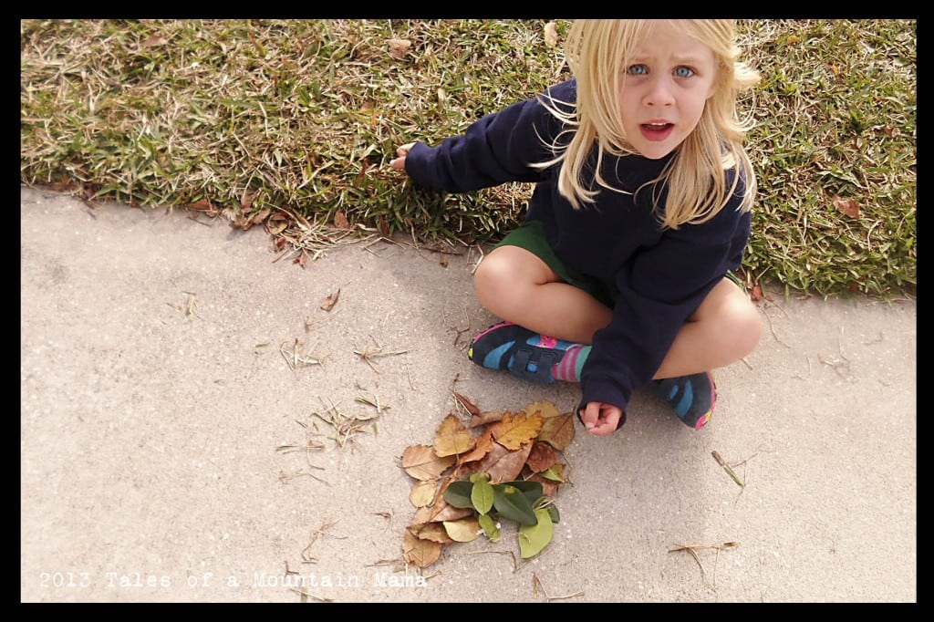 "Ava making a ""den"" with sticks and leaves"