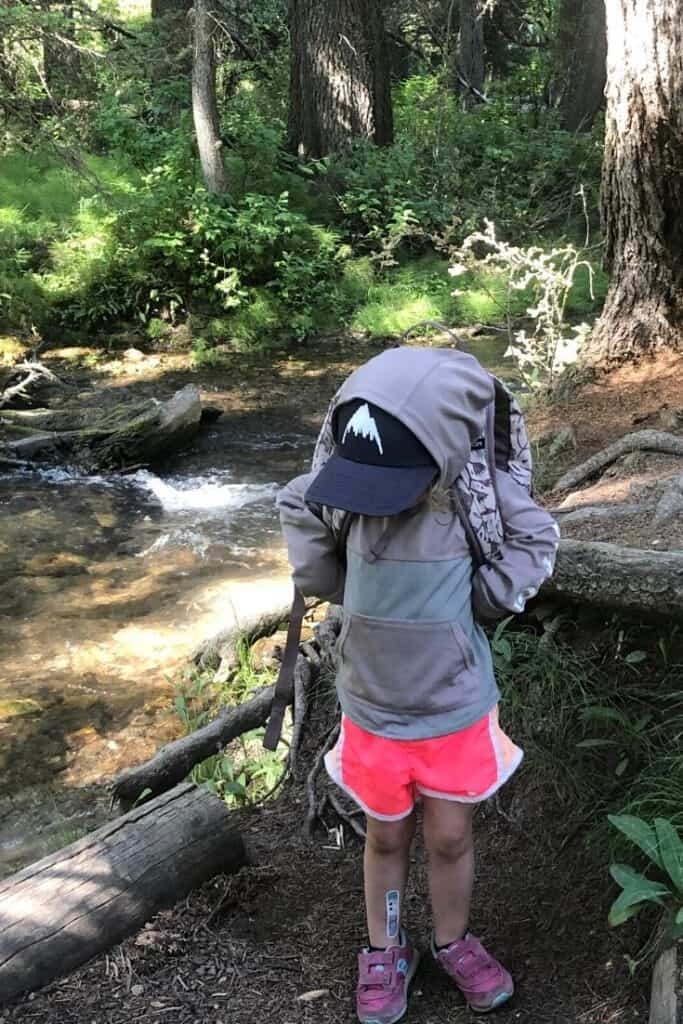 A toddler takes her backpack off in preparation of going poop in the woods.